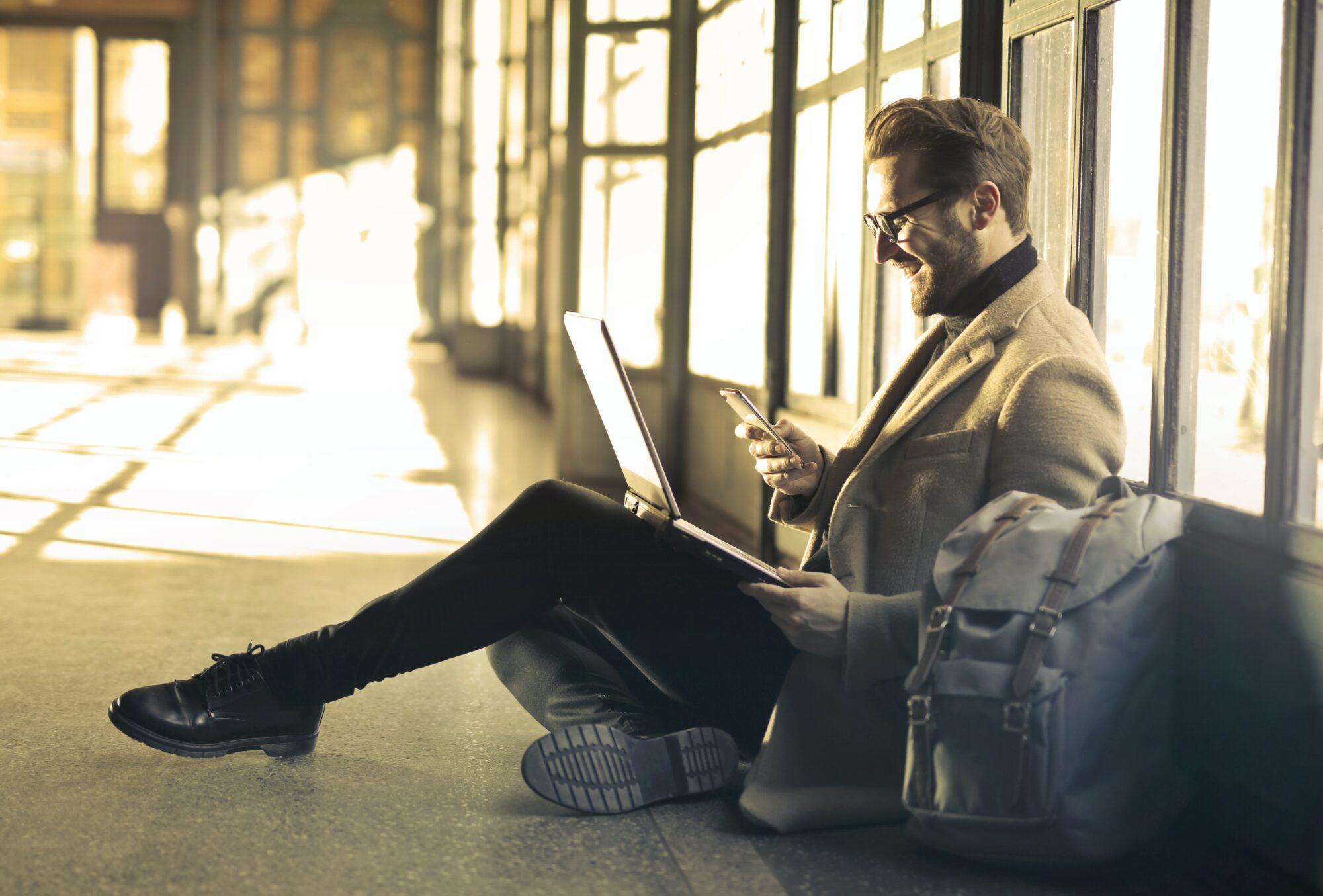 Mann sitzt mit Laptop am Boden