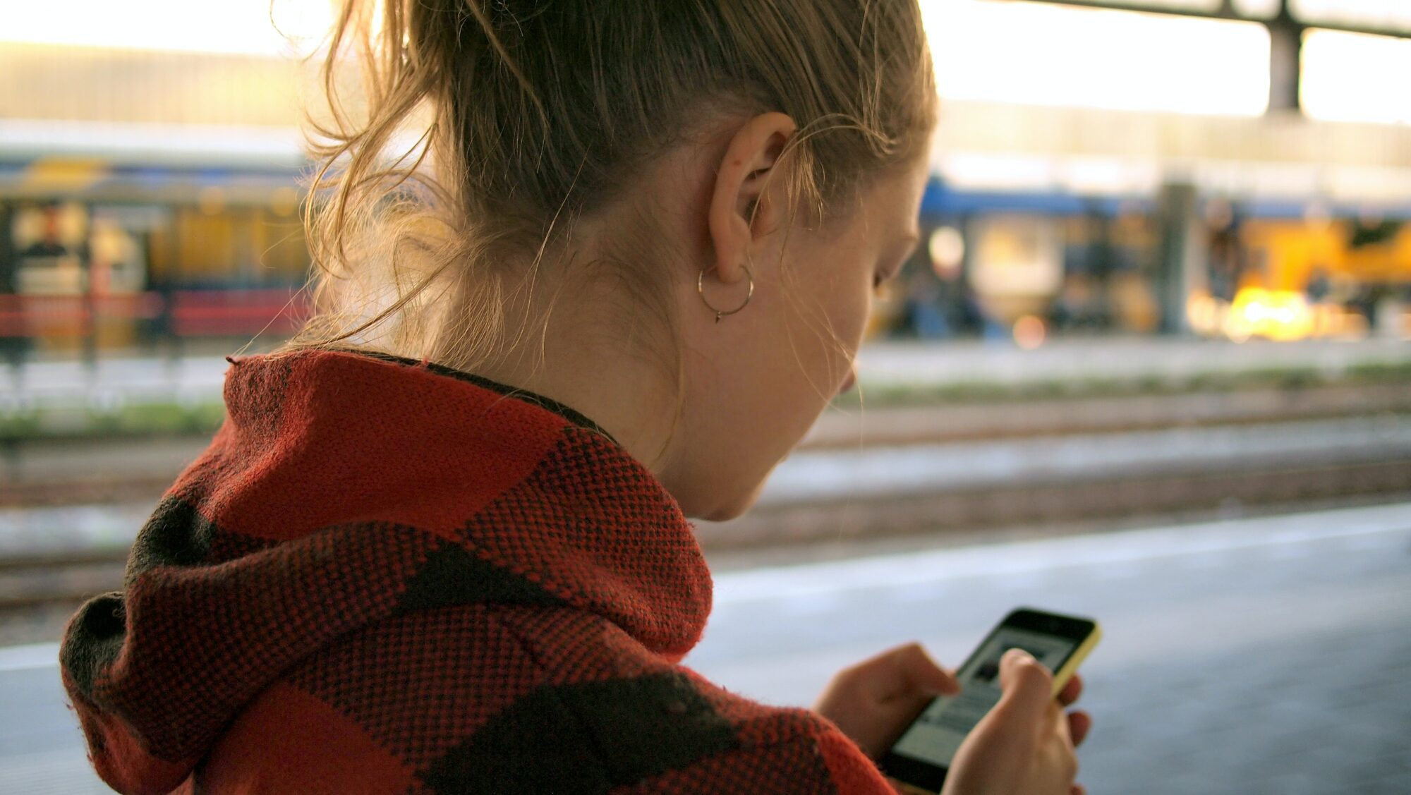 Frau mit Smartphone am Bahnsteig